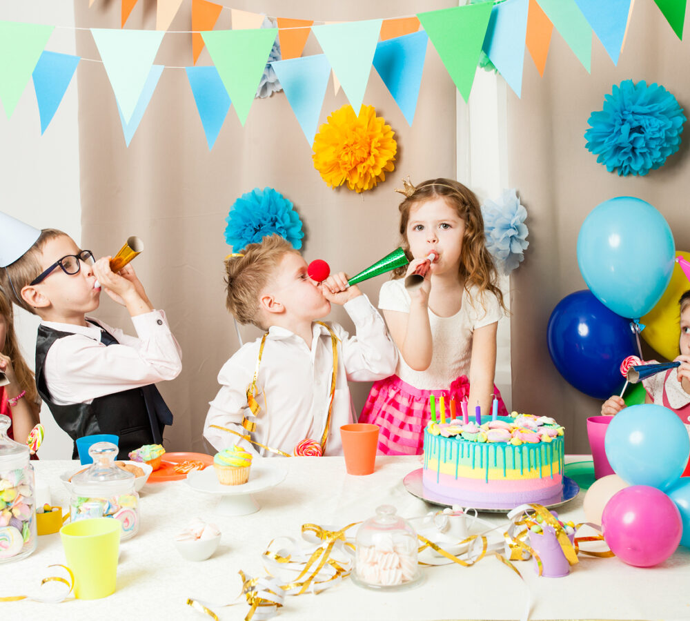 Group of smiling children playing on the birthday party in decorated room. Happy kids blowing in pipes on birthday party